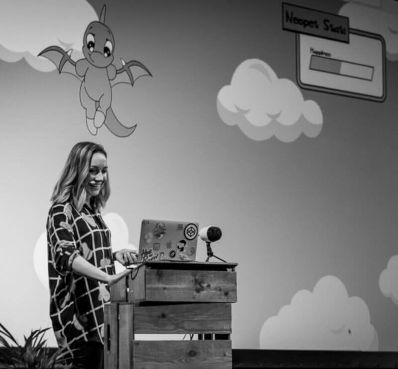 black and white photo of Cassie on stage at beyond tellerrand. Screen behind her shows an SVG neopet.